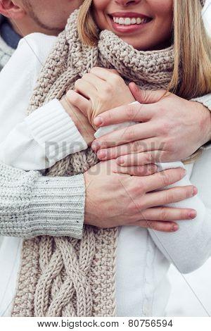 Young man embracing his girlfriend in winterwear