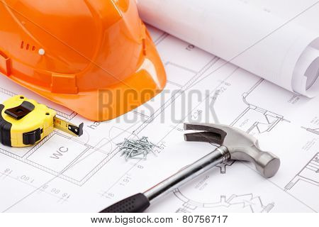 Hammer with black handle, tape measure, orange hard hat and nails on the draft