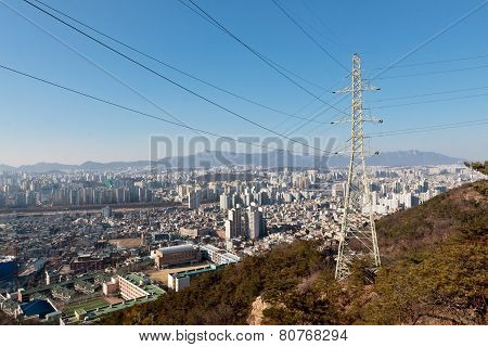Power transmission line pole and wires on a hill over a city