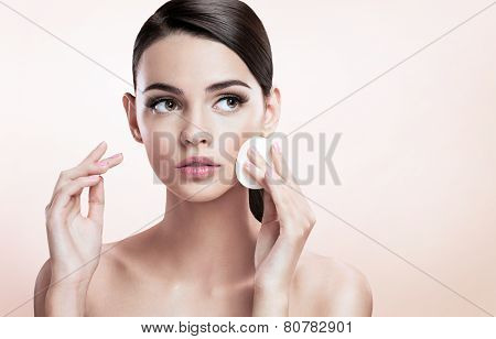 Beautiful brunette lady removing makeup from her face, skin care concept