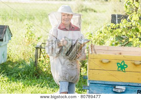 Teenage beekeeper checking hives on a bee yard poster