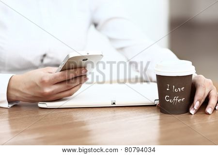 Close-up Of Woman Holding Mobile Phone In Front Of Coffee Cup