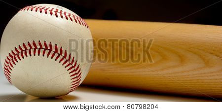 A leather baseball and wooden bat on a white background