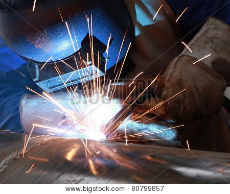 welder is welding big pipe with all safety