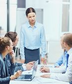 business, technology, people and management concept - strict female boss talking to business team in office poster