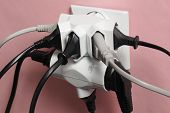 Dangerous multiple electric plugs in wall outlet poster