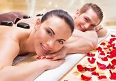 Portrait of happy smiling couple relaxing in spa salon with hot stones on body.  poster