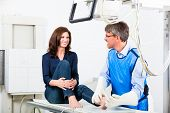 Orthopedist doctor making x-ray of patient leg in surgery poster