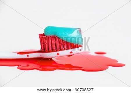 Blood and toothpaste on the toothbrush. Closeup. Isolated on white