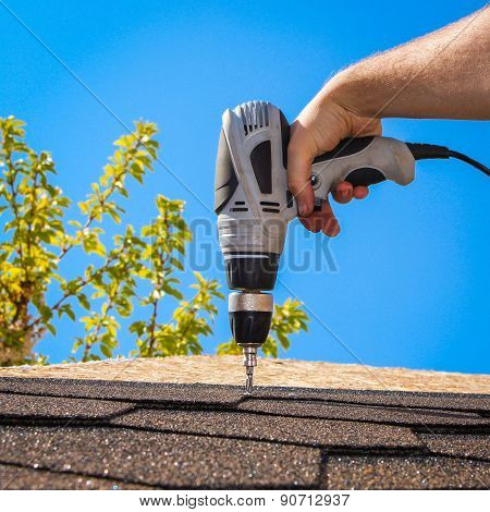 The man puts a soft roof on a house roof. The construction of houses, roofs. Builder twists the scre
