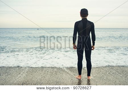 Surfer Sports Man Wearing Surfing Neoprene Waterproof Suits On A Sand Beach With A Blue Sky
