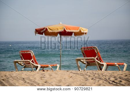 Faded And Dingy Lounger And Umbrella At The Beach.