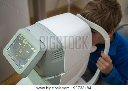 boy tests his eyes at Auto-Ref-Keratometer