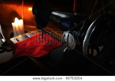 Handwheel Old Sewing Machine, Fabric And Tailoring Scissors In The Light Burning Candle. Low Key