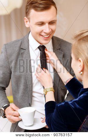 Woman fixing tie of handsome man
