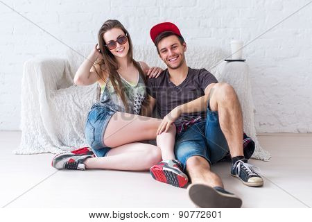 Friends girl and guy sitting on floor at home in summer jeanswear street urban casual style talking,