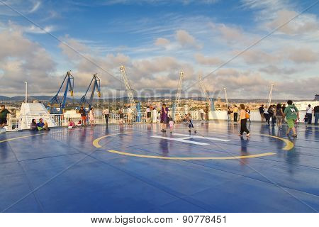 Tourists In Helipad For Helicopter On The Upper Deck Of Big Cruise Ship