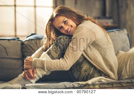 Smiling Woman On Sofa In Loft, Hugging Her Knees