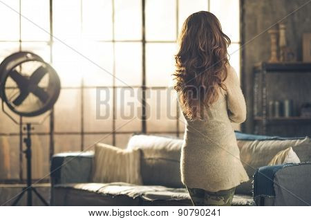 Brunette Looking Out Industrial Chic Loft Window