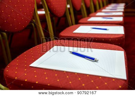 Closeup of notepad with pen for agenda on chairs in empty corporate conference room before business meeting poster