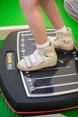 child feet on a vibrating training platform poster