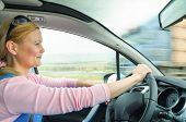 Attractive adult woman safe and carefully driving car on suburban road. Inside the auto photo with high speed oncoming lorry truck blurred in motion. poster