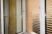 to protect against heat and sun blinds are attached to a window. poster