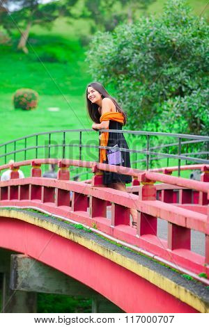 Teen Girl  At A Red Japanese Or Chinese Bhuddist Temple Bridge