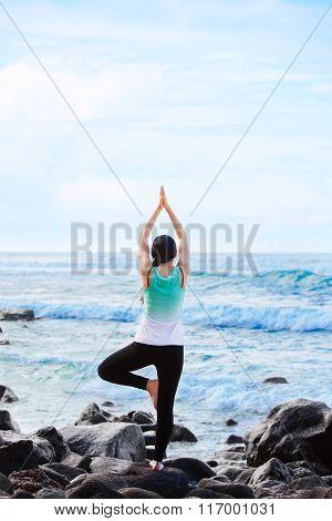 Biracial Teen Standing On Rock By Ocean Doing Yoga