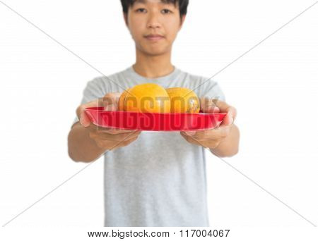 Asian guy holding oranges on tray, for offering an ancestor in Chinese new years