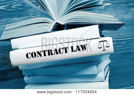 Book with Contract Law word on table in a courtroom or enforcement office. Toned image