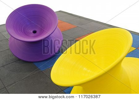 Violet And Yellow Spinning Tops In Kid Playground