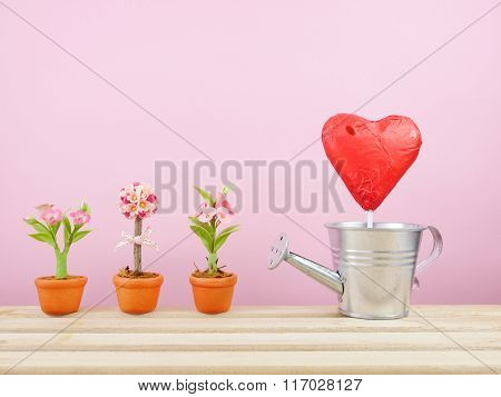 The red foiled chocolate heart stick with small silver watering can and mini fake flower