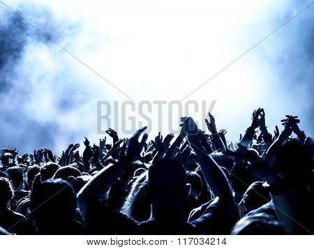 silhouettes of concert crowd in front of bright stage lights - no fine details due limited light situation