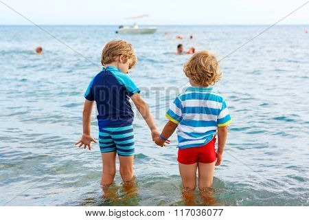 Two little kid boys taking bath in ocean