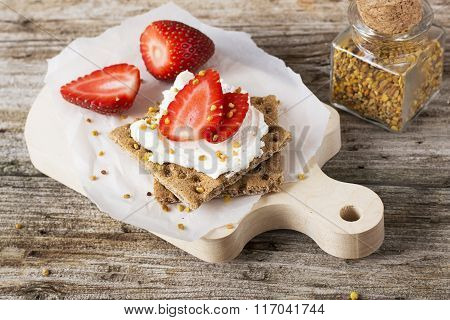 Crispy bread for breakfast for a healthy diet with curd cheese, strawberry, flower bee pollen on a wooden cutting board easy. concept of healthy family nutrition. selective Focus