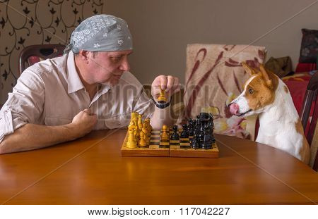 Dog and mature man playing chess in a family tournament