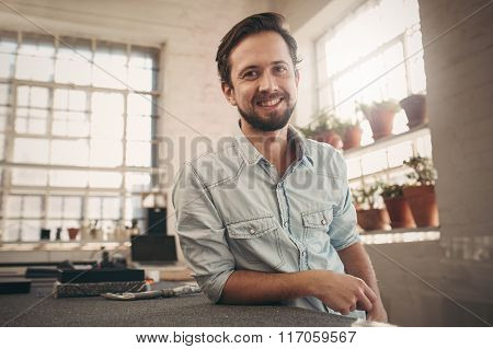 Friendly young designer looking relaxed and confident in his stu