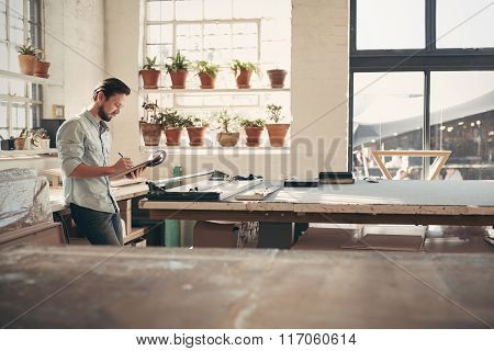 Design business owner checking stock on a clipboard