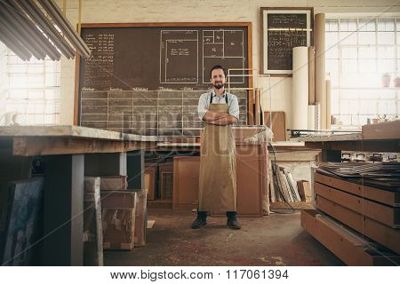 Designer craftsman standing confidently in his workshop