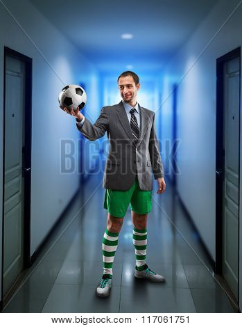 Businessman with suitcase in sportwear holding a ball in the office