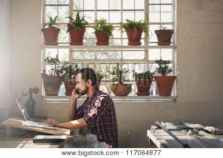 Designer entrepreneur using his phone while working on lapto