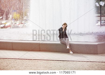 Woman Sitting By The Waterworks And Talking On The Phone