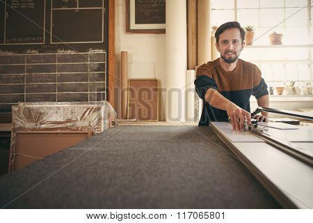 Framer looking up while using a tool on his workbench