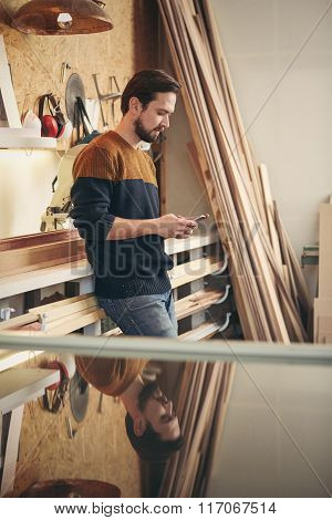 Young craftsman using phone in his workshop