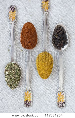 Assortment Of Powder Spices On Spoons On A Light Background