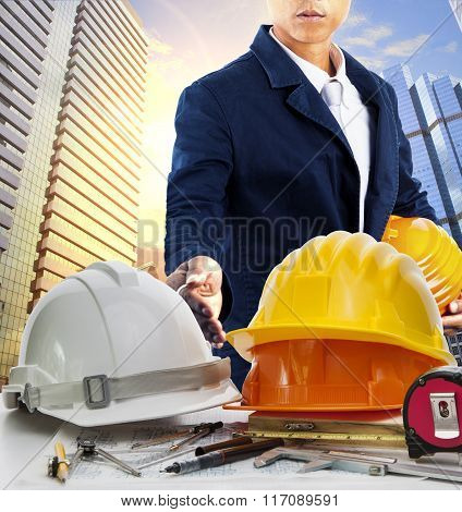 Engineer Man And Working Table Against Sky Scrapper In Urban Scene Use For Land Development And Arch