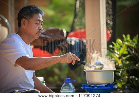 Old Man Cooking Morning Food Meal In Hot Pot On Lpg Gas Stove