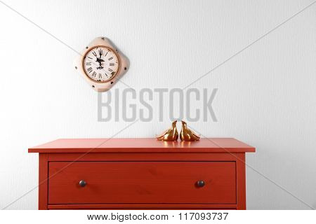 Room interior with red wooden commode and clock on light wall background