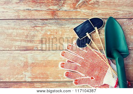 close up of trowel, nameplates and garden gloves